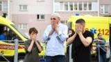 RUSSIA -- TATARSTAN -- Men pray at a makeshift memorial for victims of the shooting at School No. 175 in Kazan on May 11, 2021.