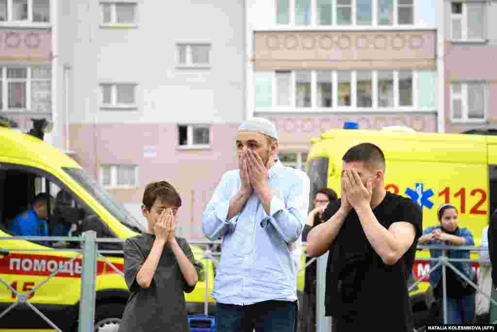 Two men and a boy pray at a makeshift memorial for victims of the shooting at Kazan's School No. 175. Islam is the most widely spread religious belief in Tatarstan.