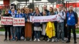 """BELARUS -- Journalists of Belarusian TUT.BY media outlet hold banners reading """"I don't protest but work"""", """"This is me at work"""", """"Freedom for journalists!"""", from left to right, as they stand in front of police station in Minsk, September 2, 2020"""