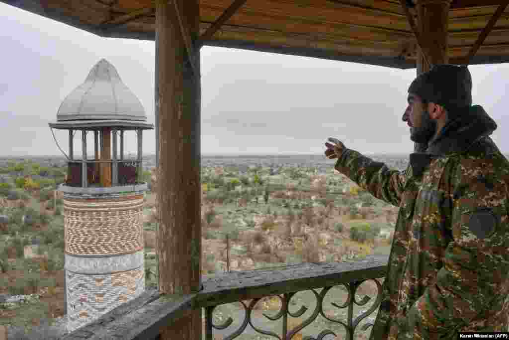 An Armenian man points toward a minaret at Agdam's 19th-century Juma mosque on November 19, 2020. The building, also known as the Agdam mosque, survived the 1992-1994 Karabakh war, but was abandoned during ethnic Armenians' occupation of the town. On November 20, 2020, Azerbaijanis attended Friday prayers in the sanctuary.