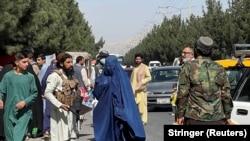"""Силы """"Талибана"""" блокируют дорогу около аэропорта, пока рядом проходит женщина, 27 августа 2021 года"""