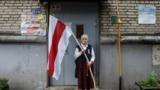BELARUS -- Nina Bahinskaya, 73, poses for a photo holding an old Belarusian national flag at an entrance of her apartment building in Minsk, September 10, 2020